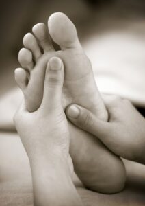 A massage therapist doing reflexology foot massage on a patient'